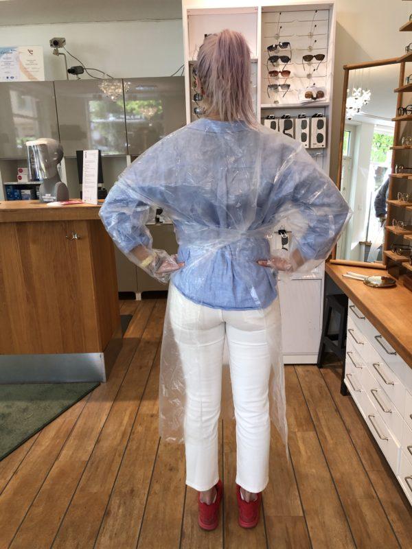 En glad optiker på Lidingö iklädd en genomskinlig regnjacka visar ryggen