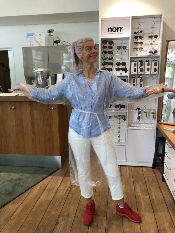 En glad optiker på Lidingö iklädd en genomskinlig regnjacka